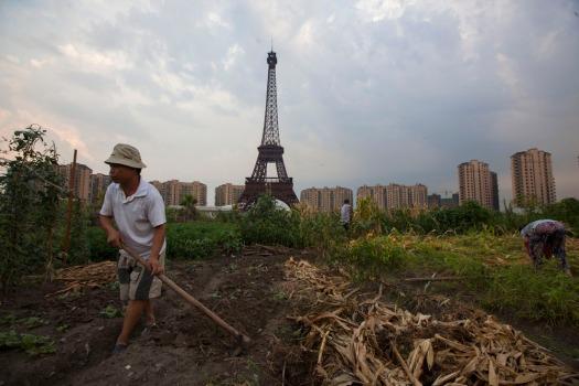Farmer tills field under a replica of Eiffel Tower at the Tianducheng development in Hangzhou